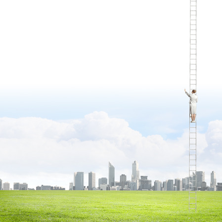 goal oriented: Businesswoman standing on ladder high above city Stock Photo