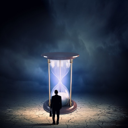 Conceptual image with sandglass and rear view of businessman Stock Photo