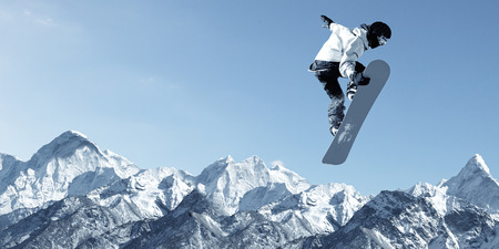 air speed: Snowboarder making high jump in clear blue sky Stock Photo