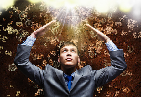 Businessman protecting head with arms from falling money symbols photo