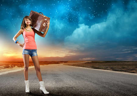 Young pretty woman tourist with suitcase with suitcase on shoulder photo