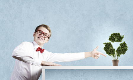 Young man in glasses and pot with recycle sign on table Stock Photo
