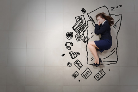 Tired businesswoman sleeping on floor and dreaming Imagens