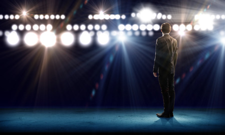 lighting effect: Rear view of businessman standing in lights of stage