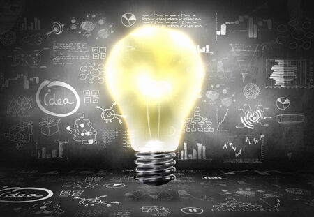 Conceptual image with light bulb and business sketches photo