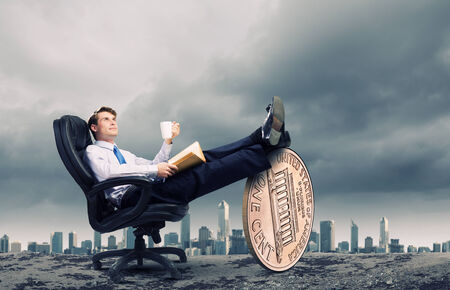 Young confident businessman sitting in chair with legs on cent coin photo
