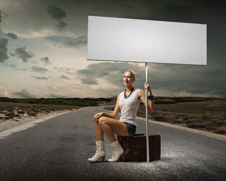 Young woman with blank banner sitting on suitcase photo