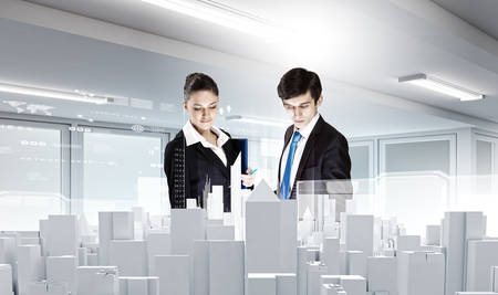 Businessman and businesswoman discussing construction model of project photo