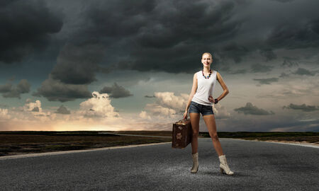 roadside stand: Young woman hiker standing with suitcase in hand Stock Photo