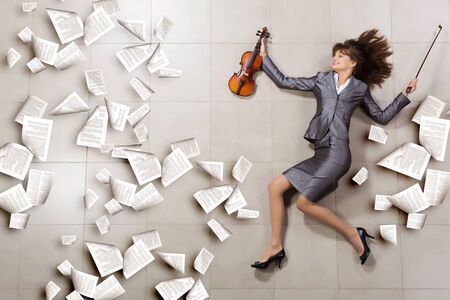Attractive businesswoman with violin in hands and papers flying in air