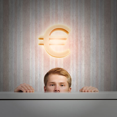 Half of face of young man looking out from under table