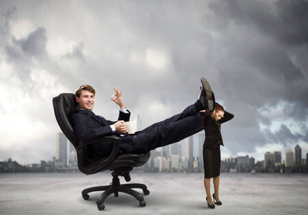 Young businessman sitting gin chair with legs on colleagues shoulders photo