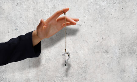 Close up of businessman hand and question sign hanging on finger photo