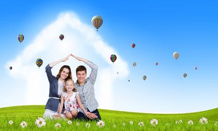 Happy family of three lying on green grass photo
