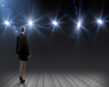 Rear view of businesswoman standing in lights of stage photo