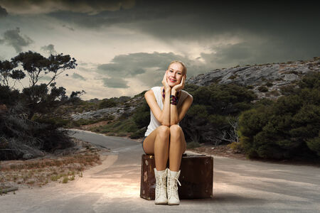 Young girl traveler in shorts sitting on suitcase photo