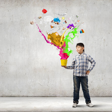 Young boy splashing colorful paint from bucket Stock Photo