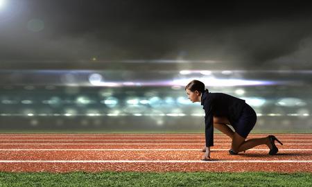 시작 위치에 서있는 경기장에서 사업가의 측면보기