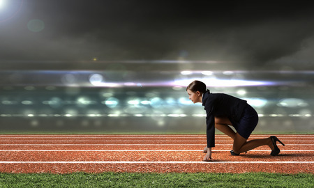 Side view of businesswoman at stadium standing in start position photo