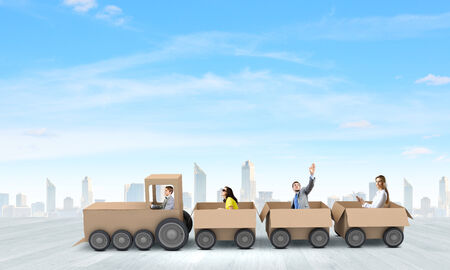 Business people riding carton train. Teamwork concept photo