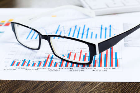 Eye glasses lying on papers with graphs and diagrams photo