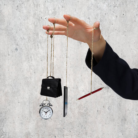 determinism: Close up of business person hand holding office items on rope