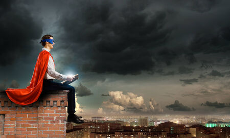 Superhero in cape and mask sitting on top of building and reading book Stock Photo