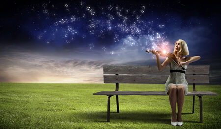 Young woman sitting on bench and playing violin photo