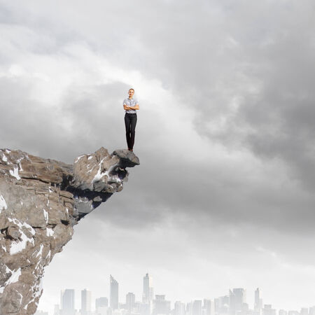 risky: Risky businesswoman standing on edge of rock Stock Photo