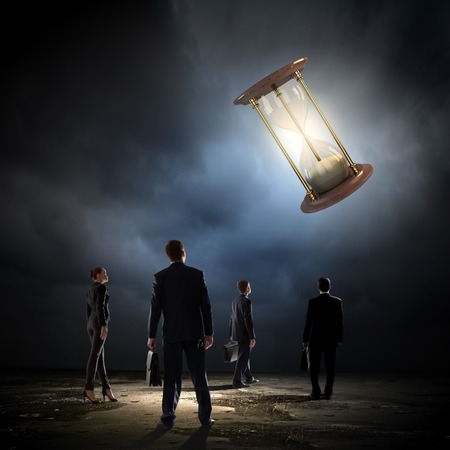 Conceptual image of business people looking at sandglass