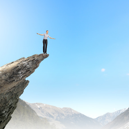 Risky businesswoman standing on edge of rock photo