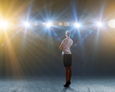 Rear view of businesswoman standing in lights of stage Фото со стока
