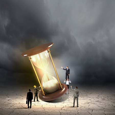 sandglass: Conceptual image of business people looking at sandglass