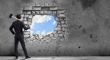 fuerza: Joven hombre de negocios decidido romper la pared con un martillo