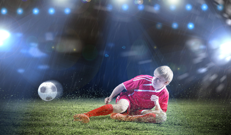 Young football player on stadium doing slide tackle