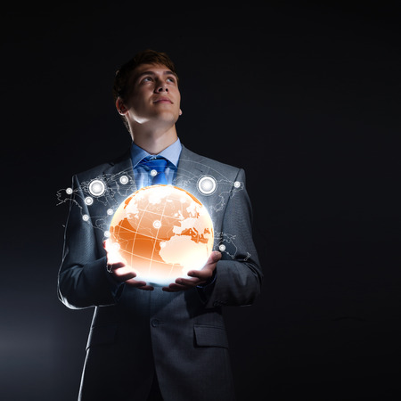 businessman carrying a globe: Young businessman holding digital globe in palm