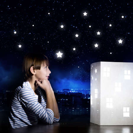 preteen model: Cute little boy looking at model of house