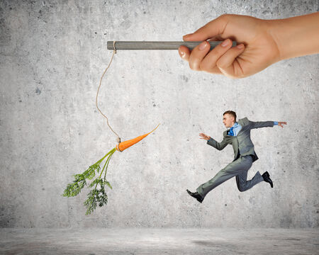 Funny image of businessman chased with carrot photo