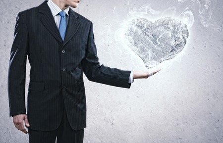 prudent: Businessman holding stone in shape of heart in palm