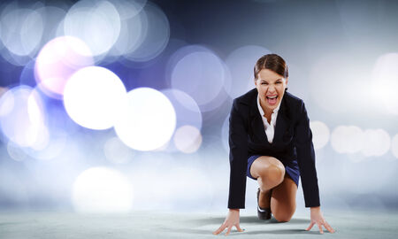 contender: Young attractive businesswoman standing in start position Stock Photo