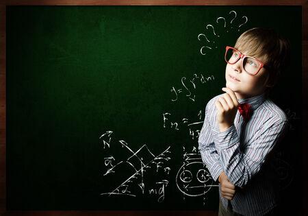 Genius boy in red glasses near blackboard with formulas photo