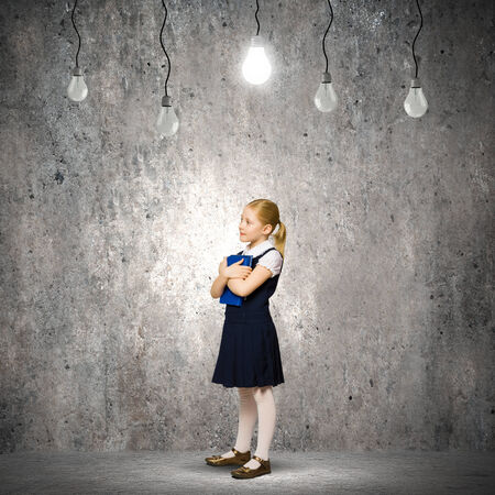 Cute school girl against grey wall with bulbs hanging above photo