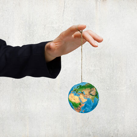 obsolescence: Close up of human hand holding Earth planet on rope. Elements of this image are furnished by NASA Stock Photo