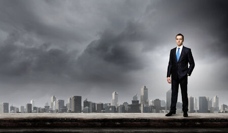 businessman standing: Young handsome businessman standing on top of building