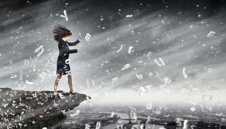 forceful: Young determined businesswoman walking against strong wind Stock Photo