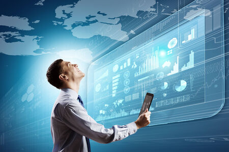 new technology: Young businessman with tablet in hands against digital background