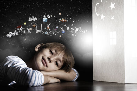 sweet dreams: Cute little boy in dark room dreaming about home and family