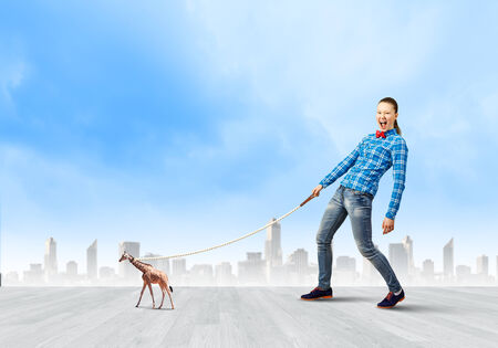 positivism: Young woman in casual holding giraffe on lead