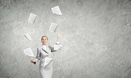 jubilate: Young pretty businesswoman juggling with paper sheets