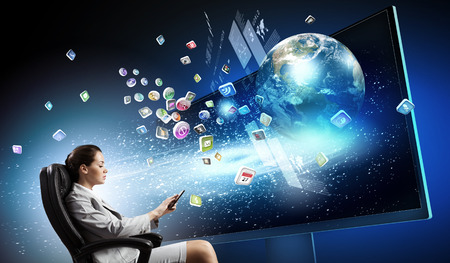 Young businesswoman in chair near tv screen with click. Banque d'images